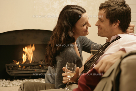 Couple hugging wine by fireplaceの素材 [FYI00901890]