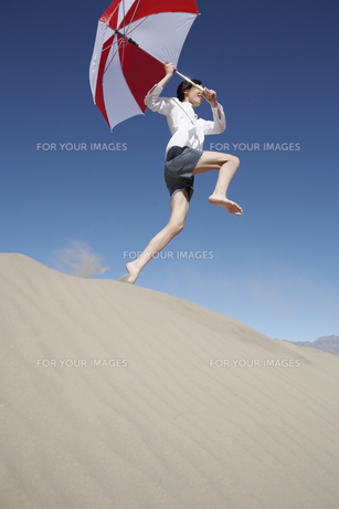Woman with umbrella jumping on sand duneの素材 [FYI00901946]