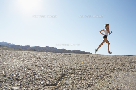 Young woman jogging in rocky landscapeの素材 [FYI00901988]
