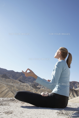 Young woman in lotus position in desertの素材 [FYI00902005]