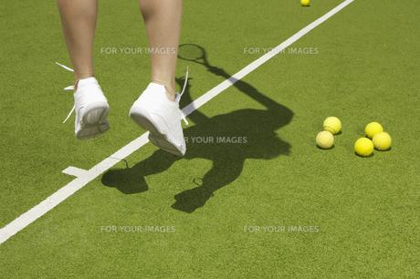 Tennis player jumping near tennis ballsの素材 [FYI00902369]