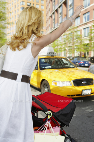 Woman with shopping bags hailing taxiの素材 [FYI00902756]