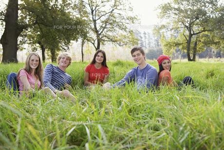 Five teenagers sitting in fieldの素材 [FYI00903273]