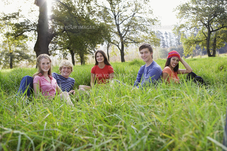 Five teenagers sitting in fieldの素材 [FYI00903274]
