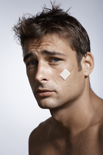 Man with adhesive plaster on cheekの素材 [FYI00903877]