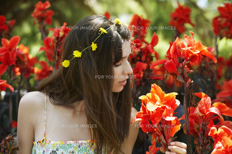 Young woman smelling red flowersの素材 [FYI00904275]