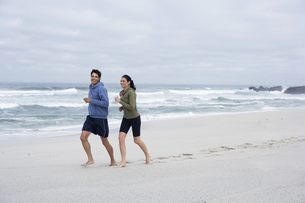 Mid adult couple running on sandy beachの素材 [FYI00904410]