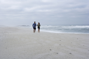 Mid adult couple running on sandy beachの素材 [FYI00904424]