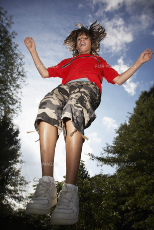 Low angle view of boy (12-13) jumpingの素材 [FYI00904640]