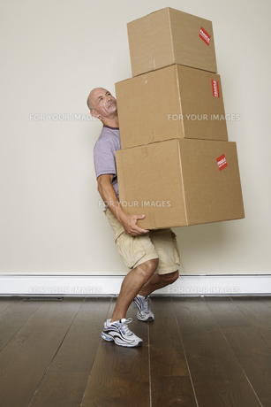 Mature man carrying stack of boxesの素材 [FYI00904678]