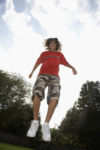 Low angle view of boy (12-13) jumpingの素材 [FYI00904686]