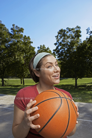Mid adult woman holding basket ballの素材 [FYI00904912]