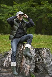 Man Using Binoculars on Tree Stumpの素材 [FYI00905042]