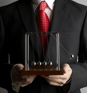 Businessman Holding Newtons Cradleの素材 [FYI00905445]