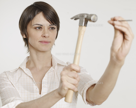 Young Woman Holding Hammer and Nailの素材 [FYI00905814]
