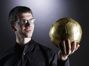 Man Holding Golden Soccer Ballの素材 [FYI00906293]
