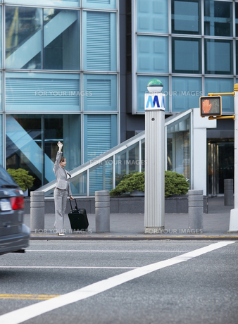 Mid-Adult Businesswoman Hailing a Taxiの素材 [FYI00906727]
