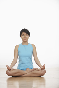 Mid Adult Woman Meditating in Lotus Positionの素材 [FYI00906921]