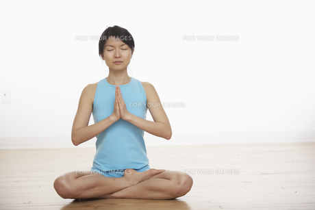 Mid Adult Woman Meditating in Lotus Positionの素材 [FYI00906952]