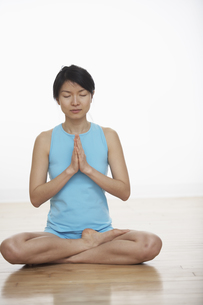 Mid Adult Woman Meditating in Lotus Positionの素材 [FYI00906965]
