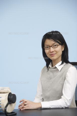 Smart Mid-Adult Woman Sitting at Deskの素材 [FYI00906971]