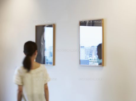 Mid-Adult Woman Walking by Wall Mirrorsの素材 [FYI00907018]