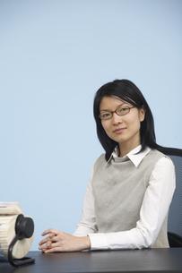 Smart Mid-Adult Woman Sitting at Deskの素材 [FYI00907026]