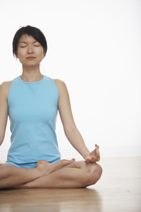 Mid Adult Woman Meditating in Lotus Positionの素材 [FYI00907052]