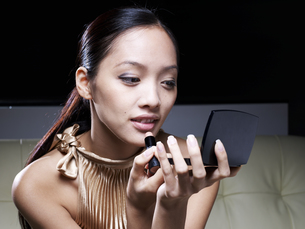 Mid-Adult Woman Applying Lipstickの素材 [FYI00907128]