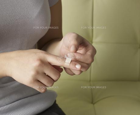Woman Putting Plaster on Fingerの素材 [FYI00907298]