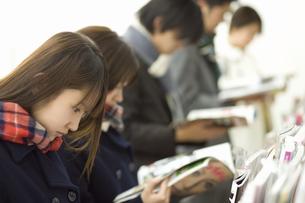 コンビニで立ち読みをする女子高生の素材 [FYI00907604]