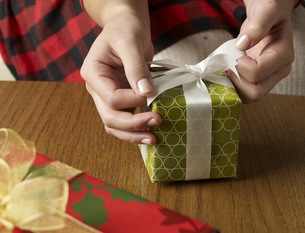 Close-Up of Woman Wrapping Christmas Presentの素材 [FYI00907615]