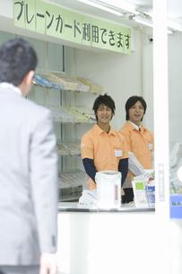 挨拶をするコンビニの店員と男性客の素材 [FYI00907733]