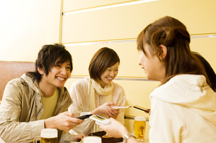 携帯電話のアドレス交換をする若者たちの素材 [FYI00908474]