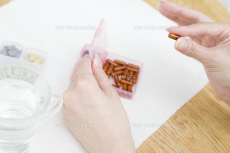 サプリメントを手にする女性の手元の素材 [FYI00908835]