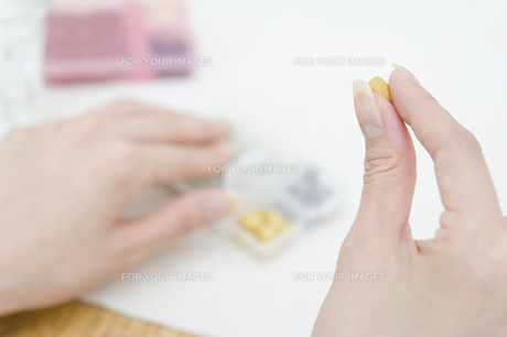 サプリメントを手にする女性の手元の素材 [FYI00908880]