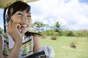 ゴルフカートに乗って電話をする女性ゴルファーの素材 [FYI00911349]