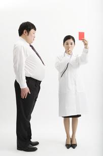 肥満男性にレッドカードを出す医者の素材 [FYI00911612]