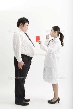肥満男性にレッドカードを出す医者の素材 [FYI00911638]