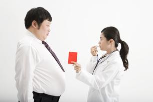 肥満男性にレッドカードを出す医者の素材 [FYI00911667]