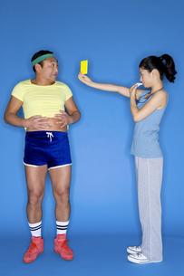 男性にイエローカードを差し出す女性の素材 [FYI00911814]