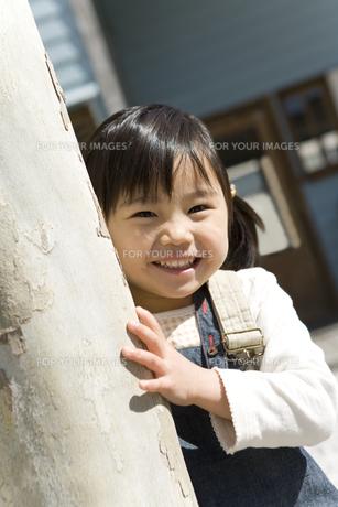 木の陰から顔を出す女の子の素材 [FYI00911990]