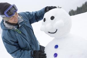雪だるまを作る男性の素材 [FYI00912080]