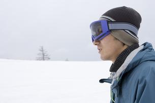 ゴーグルを着けて雪原に佇む男性の横顔の素材 [FYI00912125]