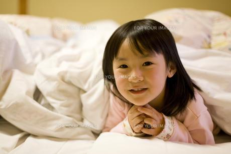 布団に入る笑顔の女の子の素材 [FYI00912202]