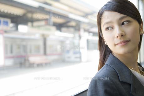 電車の中から窓の外を眺めるOLの素材 [FYI00912271]
