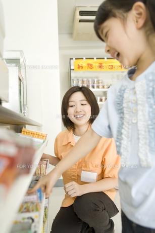 コンビニで買い物をする女の子と店員の素材 [FYI00912405]