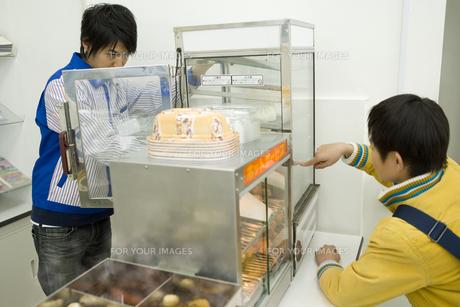 コンビニで肉まんを買う男の子の素材 [FYI00912539]