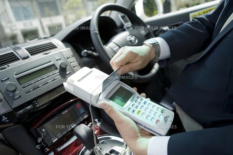 タクシー運賃をカード精算する運転手の手元の素材 [FYI00912692]