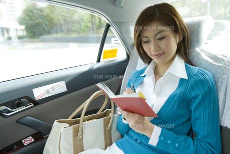 タクシーの中でメモをとるOLの素材 [FYI00912694]